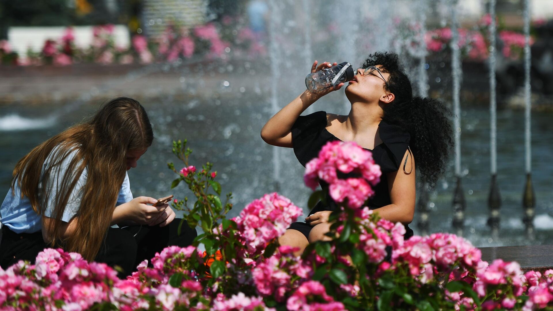 Люди отдыхают у фонтана в жаркий день на территории парка ВДНХ в Москве - РИА Новости, 1920, 07.05.2021