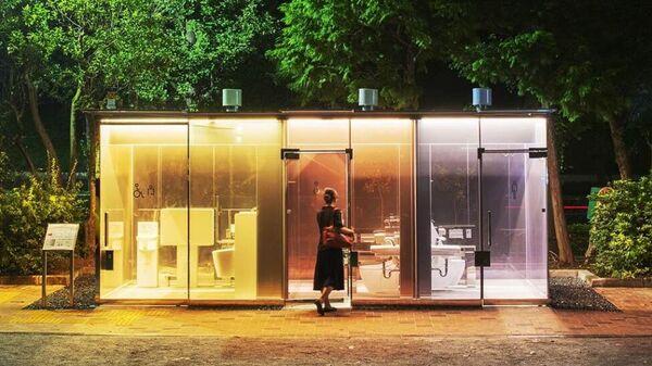 Общественный туалет с прозрачными внешними стенами в парке Токио, Япония