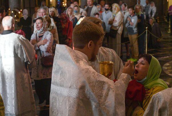 Верующие причащаются на праздничном богослужении в честь Преображения Господня в Казанском соборе в Санкт-Петербурге