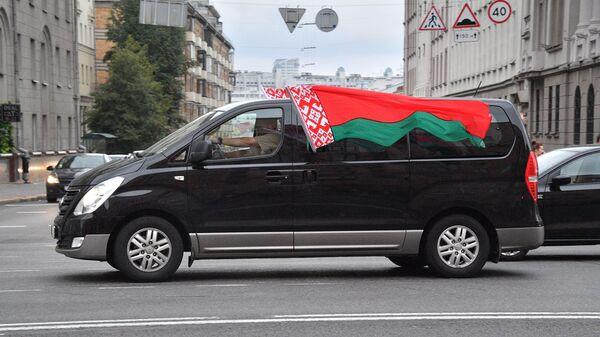 Машина с государственными флагами Республики Беларусь на проспекте Независимости
