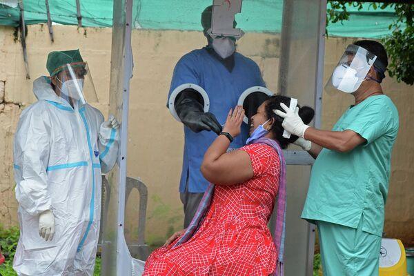 Медицинские работники берут мазок на коронавирус у женщины в Хайдарабаде