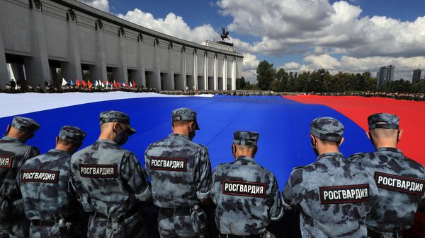 Военнослужащие разворачивают триколор у музея Победы на Поклонной горе в Москве во время празднования Дня Государственного флага РФ