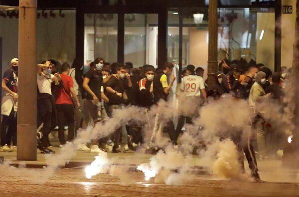 Полиция Парижа разгоняет футбольных болельщиков на Елисейских полях с помощью слезоточивого газа
