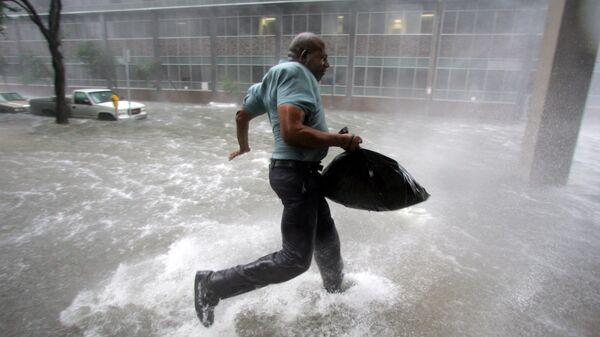 Мужчина бежит к стадиону Супердоум во время урагана Катрина в Новом Орлеане