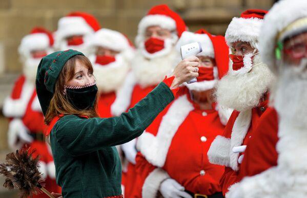 Женщина в костюме эльфа измеряет температуру посетителям школы Санта-Клауса в Лондоне, Великобритания
