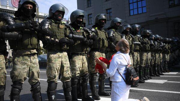 Участница акции протеста и сотрудники правоохранительных органов на проспекте Независимости в Минске