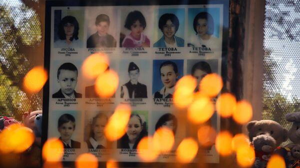 Свечи и игрушки у фотографий погибших в помещении бывшей Бесланской школы №1