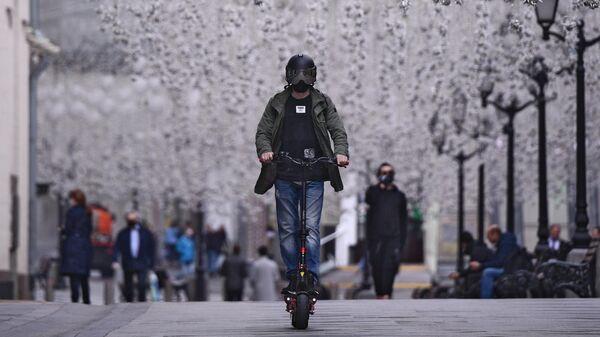 Мужчина в защитном шлеме катается на электросамокате