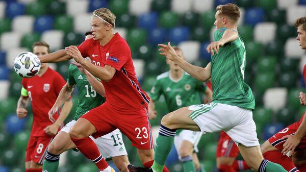 Нападающий сборной Норвегии по футболу Эрлинг Холанд (слева) и защитник сборной Северной Ирландии Дэниел Баллард