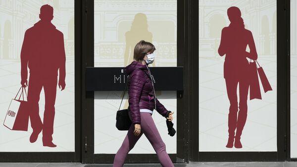 Девушка проходит мимо ГУМа в Москве