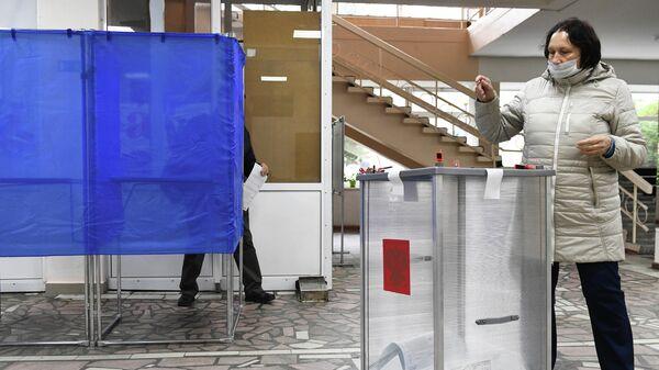 Женщина голосует на выборах губернатора Иркутской области на избирательном участке в Иркутске