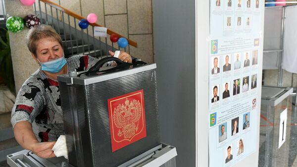 Член участковой избирательной комиссии дезинфицирует урны для голосования