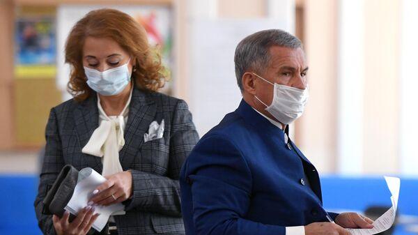 Действующий президент Республики Татарстан Рустам Минниханов с супругой Гульсиной во время голосования на избирательном участке №42 в Казани