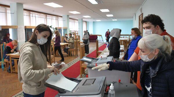 Девушка голосует на избирательном участке в Архангельской области