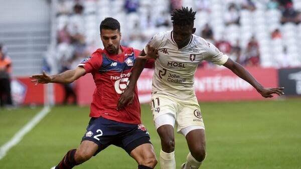 Lille's Turkish defender Zeki Celik (L) fights for the ball with Metz's Senegalese forward Opa Nguette during the French L1 football match between Lille (LOSC) and FC Metz at the Pierre Mauroy Stadium in Villeneuve d'Ascq on September 13, 2020. (Photo by FRANCOIS LO PRESTI / AFP)