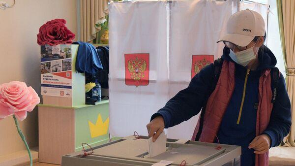 Девушка опускает бюллетень в урну на избирательном участке во время выборов губернатора Ленинградской области