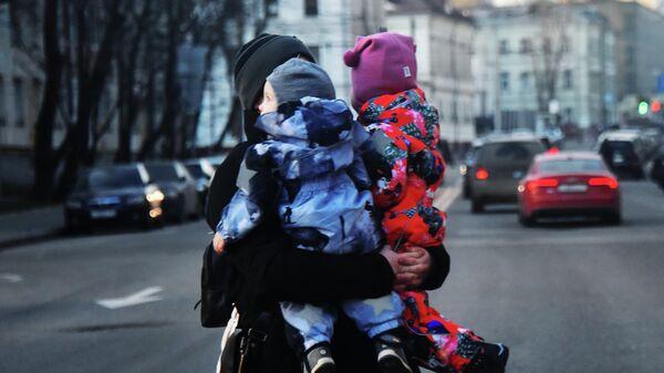 Женщина с двумя детьми на руках переходит дорогу.