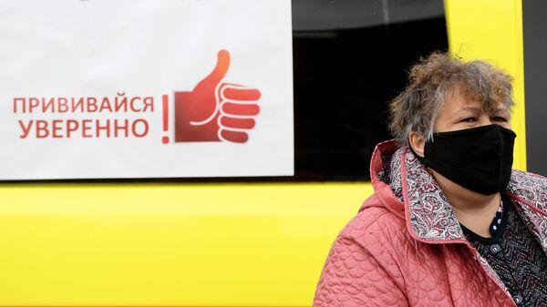 Жительница Казани у машины скорой помощи, где проходит бесплатная вакцинация от гриппа