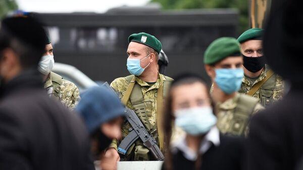 Украинские пограничники и паломники-хасиды на нейтральной полосе белорусско-украинской границы между пунктами пропуска Новая Гута и Новые Яриловичи