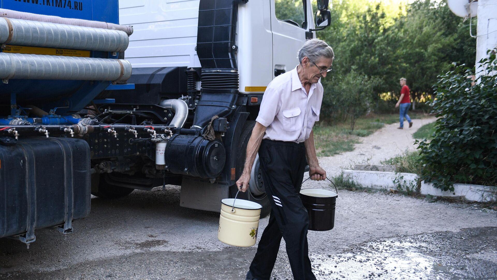 Житель Cимферополя набирает в емкости питьевую воду, привезенную в цистернах - РИА Новости, 1920, 11.10.2020