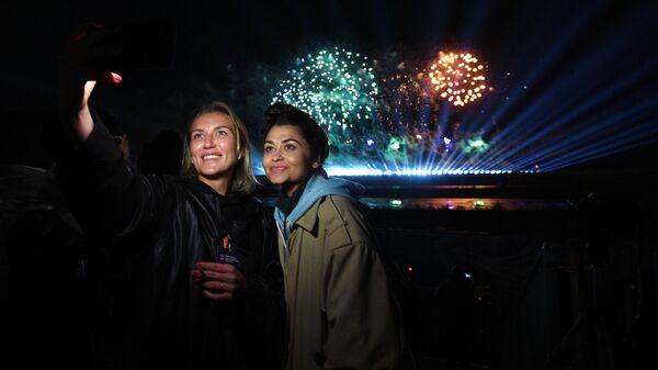 Девушки фотографируются на фоне салюта на международном фестивале фейерверков Ростех, который проходит на территории парка Патриот
