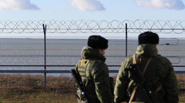 Российские пограничники у заграждения