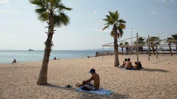 Туристы на пляже в пригороде Афин