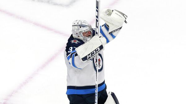 EDMONTON, ALBERTA - AUGUST 03: Connor Hellebuyck #37 of the Winnipeg Jets celebrates the win over the Calgary Flames during Game Two of the Western Conference Qualification Round prior to the 2020 NHL Stanley Cup Playoffs at Rogers Place on August 03, 2020 in Edmonton, Alberta. The Winnipeg Jets defeated the Calgary Flames 3-2.   Jeff Vinnick/Getty Images/AFP
