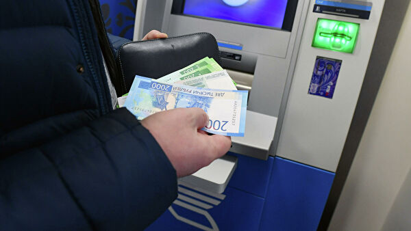 Женщина производит снятие денег в банкомате