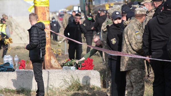 Люди несут цветы на место крушения самолета Ан-26 под Харьковом