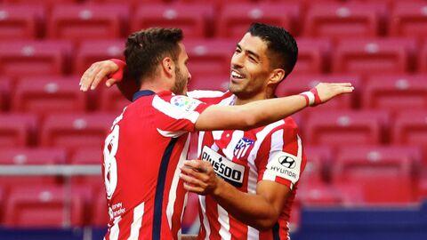 Футболисты мадридского Атлетико Сауль и Луис Суарес радуются забитому мячу