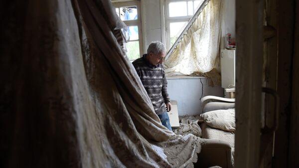 Местный житель показывает комнату пострадавшего после обстрелов дома в городе Мартуни непризнанной Нагорно-Карабахской Республики
