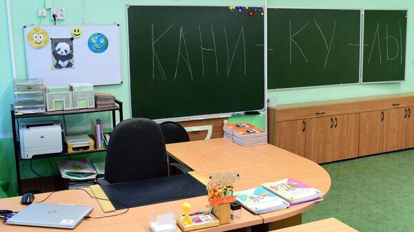 Надпись Каникулы на школьной доске в учебном классе в московской школе