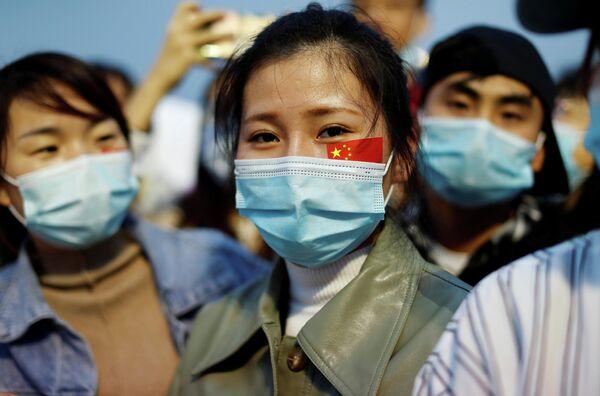 Люди в защитных масках на церемонии поднятия государственного флага на площади Тяньаньмэнь по случаю 71-й годовщины образования КНР в Пекине