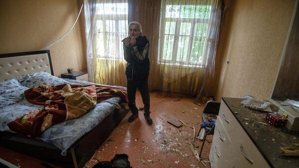 Мужчина показывает дом, поврежденный в результате обстрела по общине Иванян Нагорного Карабаха
