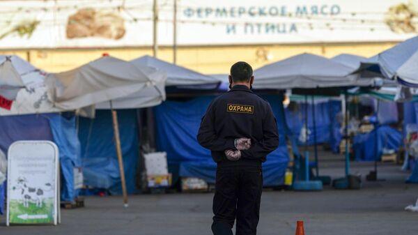 Охранник на территории продовольственного рынка Ветерок, закрытого из-за нарушения масочного режима