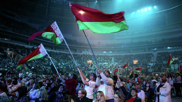 Участники форума в Минске с флагами Белоруссии во время выступления президента Белоруссии Александра Лукашенко