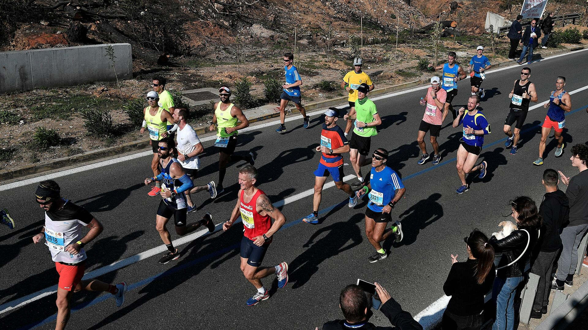 Athletes run past burned out area near the village of Mati during the  36th Athens Classic Marathon 'The authentic' from the town of Marathon to the Panathenaic stadium in Athens on November 11, 2018. (Photo by Louisa GOULIAMAKI / AFP) - РИА Новости, 1920, 02.10.2020