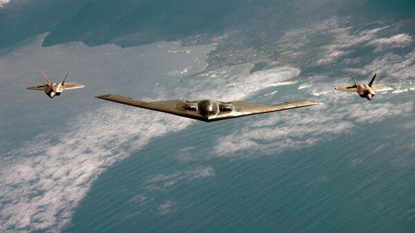 Американский малозаметный стратегический бомбардировщик Northrop B-2 Spirit в сопровождении истребителей F-22 Raptor