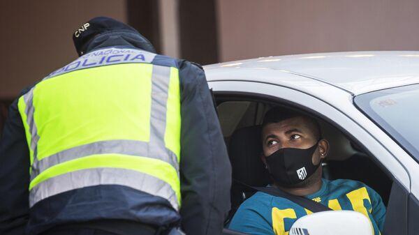 Сотрудник полиции общается с водителем автомобиля на контрольно-пропускном пункте при въезде в Мадрид
