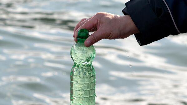 Сотрудник Следственного комитета России по Камчатскому краю берет пробу морской воды