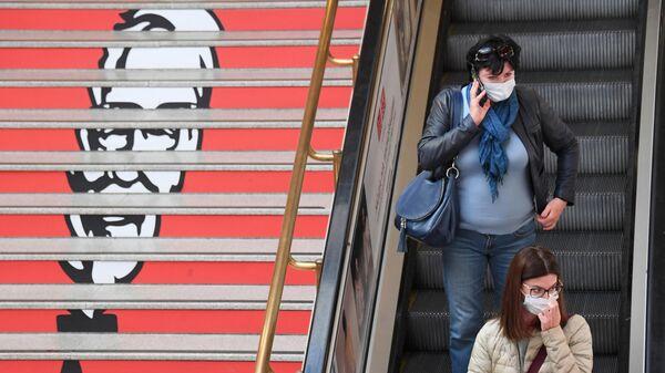 Пассажиры на эскалаторе в торговом центре в Москве