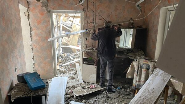 Мужчина осматривает комнату дома в Степанакерте, разрушенного после обстрела