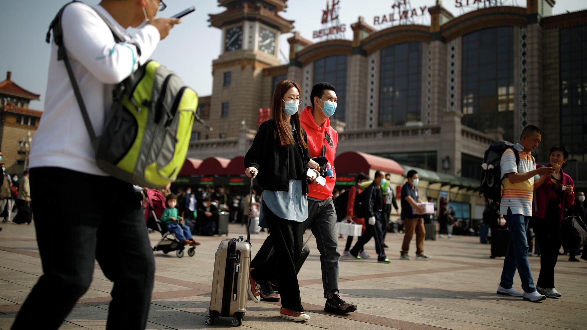 Люди с защитных масках возле железнодорожного вокзала в Пекине  - РИА Новости, 1920, 10.10.2020