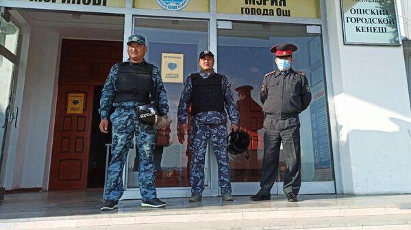 Сотрудники правоохранительных органов у входа в здание мэрии в Оше