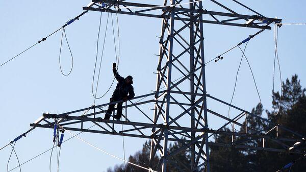 Рабочий монтирует высоковольтную линию электропередач