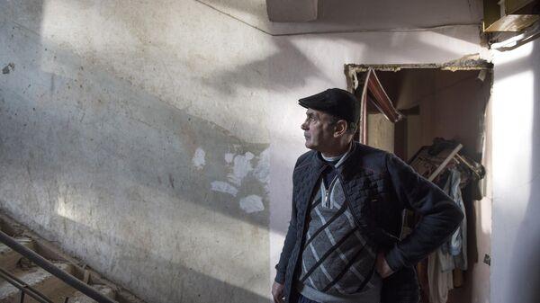 Местный житель в разрушенном доме в городе Степанакерт, который подвергся обстрелу