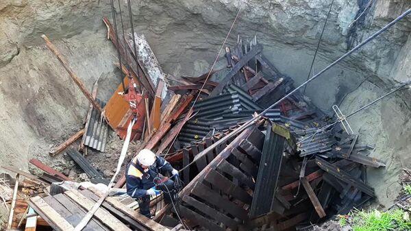 Сотрудник МЧС РФ разбирает завалы, провалившегося под землю жилого дома в Брянской области
