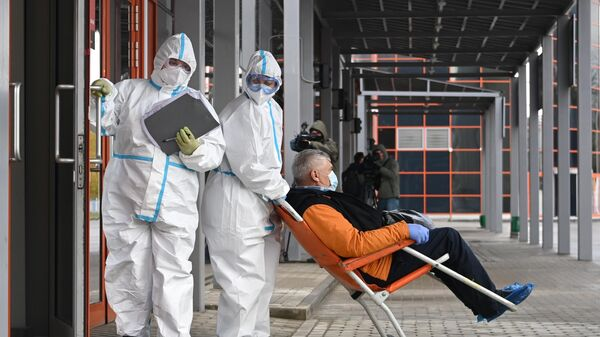 Сотрудники скорой помощи доставляют пациента во временный госпиталь COVID-19 на ВДНХ