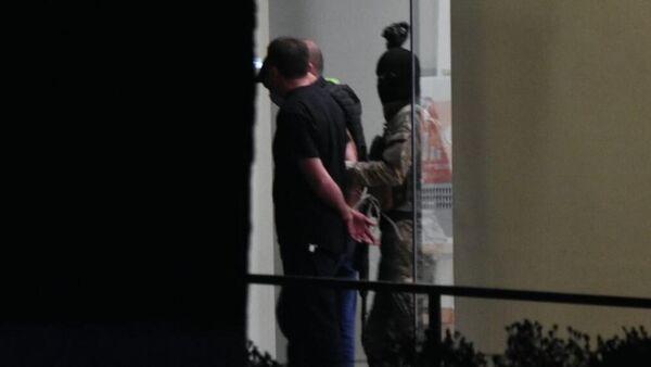 Вооруженный мужчина вместе с тремя заложниками покидает отделение Банка Грузии в Зугдиди